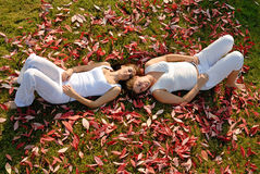 2 girlfriends lying down between autumn leaves Stock Images