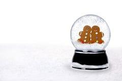2 glückliche Lebkuchen-Leute innerhalb eines Snowglobe Stockbild
