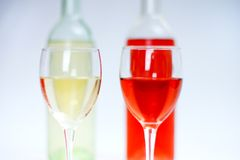 2 glasses of white and rose wine with bottles and white background stock photos