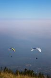 2 Gleitschirme, die in den hohen Nebel fliegen Lizenzfreie Stockfotografie