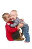 2 hermanos que abrazan Eachother en el fondo blanco Imagen de archivo