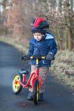 2 jaar oude peuter die op zijn eerste fiets berijdt Stock Foto