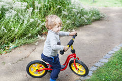 2 Jahre altes Kleinkindreiten auf seinem ersten Fahrrad Stockbild