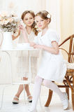2 little sisters in cafe. 2 little girls in white dresses sitting in cafe and looking at you Stock Photo