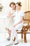 2 little sisters in cafe. 2 little girls in white dresses sitting in cafe and looking at you Royalty Free Stock Photo