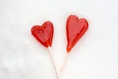 2 lollipops формы сердца красных на снежке Стоковая Фотография