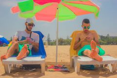 2 Man Sitting on White Beach Lounger With Green and Pink Patio Umbrella in Between Stock Photos