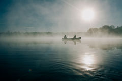 2 Men on Boat at Calm Foggy Lake during Daytime Stock Images