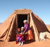 2 mujeres de Navajo fuera de su choza tradicional de Hogan Imagen de archivo