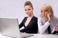 2 mujeres están trabajando con la computadora portátil Imágenes de archivo libres de regalías