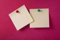 2 note adesive gialle in bianco su colore rosso Immagini Stock