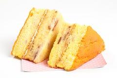 2 partes de bolo amarelo em um fundo branco Imagem de Stock