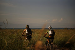 2 People Riding a Bike in the Field Royalty Free Stock Photos