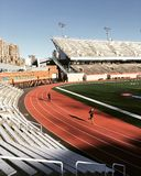 2 People Running on Stadium Race Track during Daytime With Blue Clear Skies Stock Image