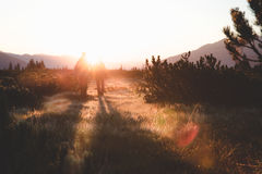 2 People Walking on Grass Field in Front of Mountain during Sunrise Royalty Free Stock Images