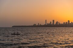 2 Person on the Boat on the Ocean in Front Urban City during Golden Hour Royalty Free Stock Images