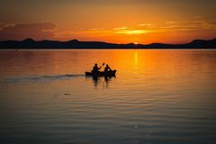 2 Person on Boat Sailing in Clear Water during Sunset Stock Photos