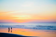 2 Person With Dog by the Seashore during Dawn Stock Image
