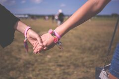 2 Person Holding Each Other Wearing Pink Friendship Bracelet during Daytime Royalty Free Stock Photo