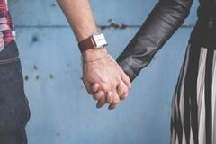 2 Person Holding Hands Besides Blue Painted Wall Stock Photos