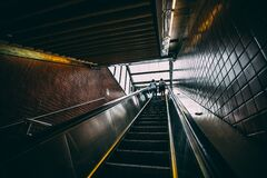 2 Person Standing on Black Escalator during Daytime Royalty Free Stock Images