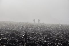 2 Persons Walking on Black Rock Under Fogs during Daytime Stock Photo