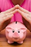 2 руки над piggy банком Стоковые Фотографии RF