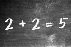 2 plus 2 equals 5. 2+2=5 written on blackboard in chalk Stock Photos