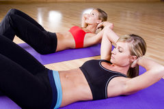 2 pretty girls doing sit-ups Royalty Free Stock Photos