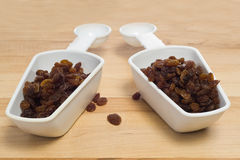 2 Scoops Of Raisins. Two measuring cups full of raisins, shot on a wooden board Royalty Free Stock Image