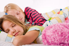 2 sleeping princesses. Two young children enjoying their colorful bed royalty free stock images