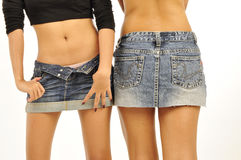 2 slim girls wearing short denim skirts Royalty Free Stock Photo