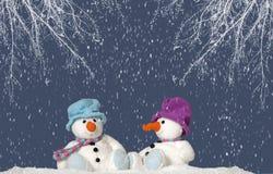 2 sneeuwmanzitting in de sneeuw Stock Foto's