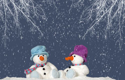 2 snowman sitting in the snow Stock Photos