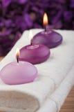 2 stearinljus masserar den purpura handduken Royaltyfria Bilder