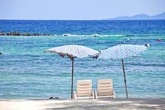 2 stolar på strand framme av havet Royaltyfri Bild