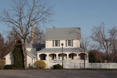 2-storey white house. With white wooden fence, trees and street lamp Royalty Free Stock Images