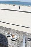 2 tazas vacías del coffe en bech en la playa Imágenes de archivo libres de regalías