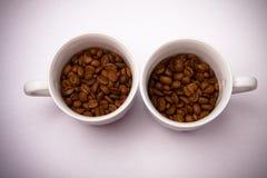 2 tazze con i chicchi di caffè Fotografia Stock