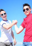 2 teen boys shaking hands. Two teenage boys shaking hands outdoor, smiling, against blue summer sky Stock Photos