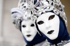 2 Venetians in carnival masks. Two Venetians in blue and silver costumes with white masks Royalty Free Stock Photo
