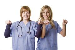 2 verpleegsters die teken houden dat op wit wordt geïsoleerda Stock Fotografie