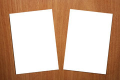 2 White A4 Page On Wood Background - Version 2. There are two white empty A4 page on a wood background that can be a desk Stock Photography