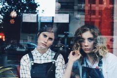 2 Woman in Blue Overalls Sitting Inside Store during Daytim Stock Photo