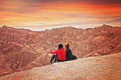 2 Woman Seating on the Mountain Cliff during Golden Hour Royalty Free Stock Images