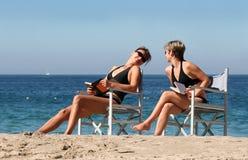 2 women on the beach. 2 women reading on the beach Stock Photo