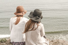 2 Women With Hats Sitting Near Shore Royalty Free Stock Photos