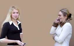 2 women with phones. Blond women with phones Stock Photography