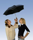 2 women under the umbrella. Women under the umbrella looking up Royalty Free Stock Photos