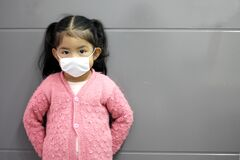 Free 2-year-old Girl With Protective Face Mask For The New Normal Of Covid-19 With Gray Wall In The Background Stock Photo - 193261360